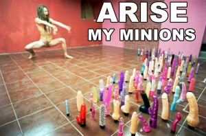 Humerously captioned image of a performance artist crouched before many dildos